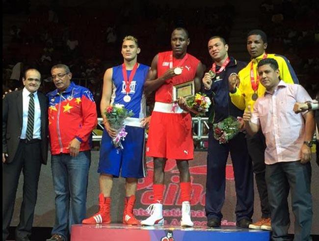 Yamil Peralta (de azul) con su medalla plateada en el podio de 91 kilos.