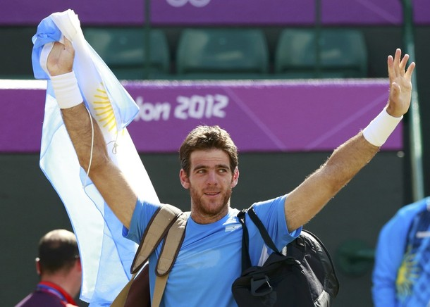 Argentina's del Potro holds his country's flag as he walks off the court after defeating Serbia's Djokovic in the men's singles tennis bronze medal match at the All England Lawn Tennis Club during the London 2012 Olympic Games